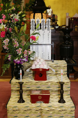 The altar devoted to our ancestors with the offering of sweets and the incense.