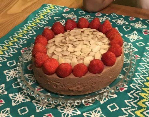 Chocolate rare cheesecake with strawberries and almonds.
