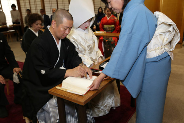 Signing our names to document our wedding at the temple.