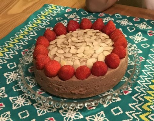 Chocolate rare cheesecake with strawberries and almonds.